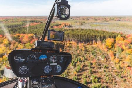 Helicopter cockpit in flight over autumn wood