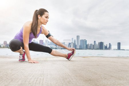 Woman doing stretching exercises with Chicago skyline on backgro