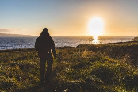 Photo for Man with backpack walking toward the sea at sunset. Explorer hiking over a cliff next to the seaside, backlight shot. Nature and adventure concepts. - Royalty Free Image