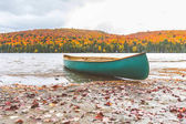 Canoe on the shore of a lake, autumn nature setting