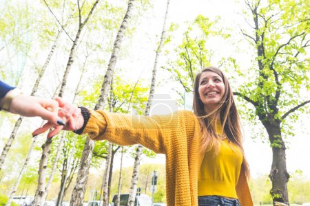 Happy woman walking with her girlfriend and smiling