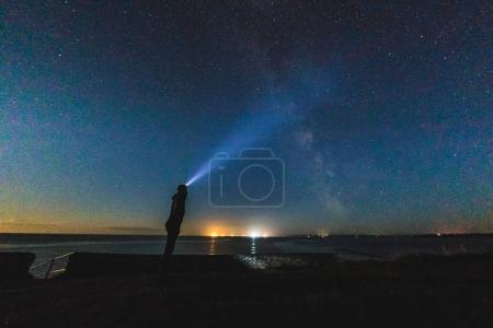 Man with headlight staring at night sky