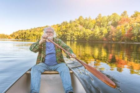 Photo for Senior man with canoe rowing on a sunny day. Man canoeing on a lake in Ontario, Canada. Typical outdoor activity, travel and leisure concepts - Royalty Free Image