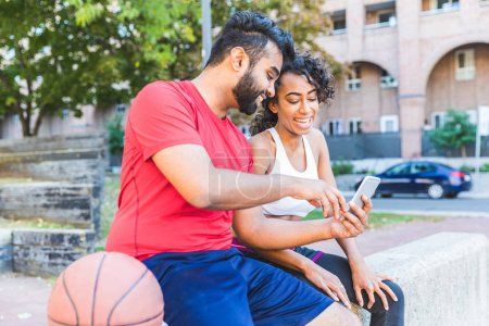 Black couple with phone and basketball at park