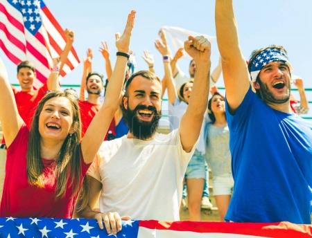 American fans cheering at stadium with USA flags