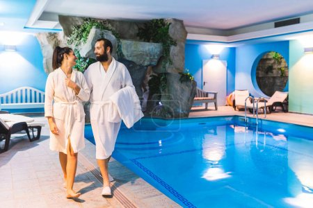 Photo for Couple in relax at therme with swimming pool. Man and woman wearing batrobe enjoying time at spa. Leisure and luxury relax concepts - Royalty Free Image