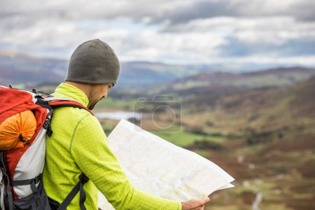 Photo for Man explorer looking a map at top of mountain hiking trail. Young man bringing a backpack and wearing a wool hat, looking at his paper map. Travel and nature concpets - Royalty Free Image