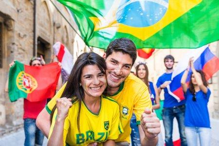 Happy Brazilian couple supporters celebrating victory