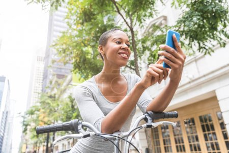 Photo for Black woman with bike typing on the phone in the city. Beautiful woman wearing a gray dress, holding her smartphone and moving around in the city in a eco friendly way. Lifestyle and relax concepts - Royalty Free Image