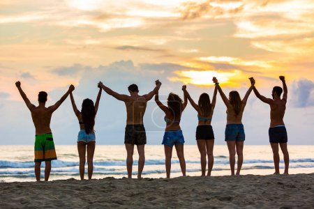 Group of friends raising hands on the beach at sunset