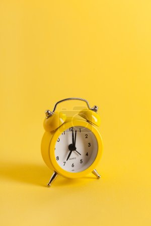 Photo for Yellow alarm clock on yellow background - Royalty Free Image