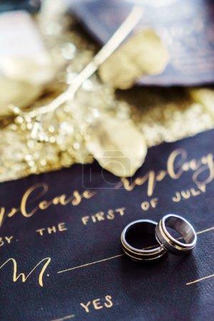 Photo pour Anneaux de mariage brillant sur la carte de mariage - image libre de droit