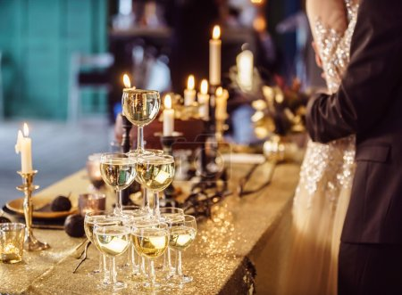 Couple by champagne glasses tower