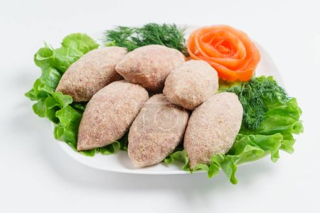 Raw cutlets with salad leaves  on plate...