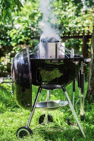 Photo pour Gros plan de grille noire avec de la fumée sur l'herbe - image libre de droit