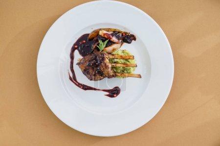 venison carree on white plate