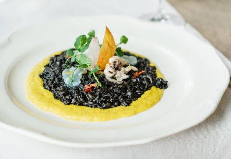 Photo for Squidink risotto on white plate, close up view - Royalty Free Image
