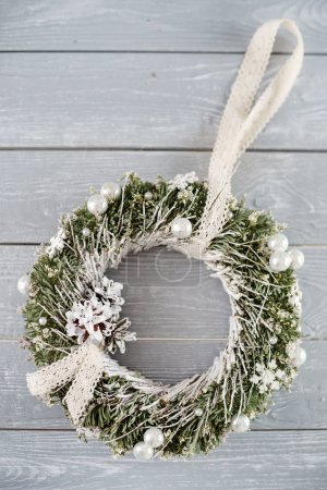 Christmas wreath on grey background, close up