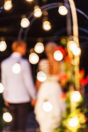 bright bulbs and bride and groom on background