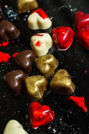 chocolate hearts on black background, close up