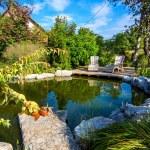 Deckchairs near pond in a beautiful creative lush ...