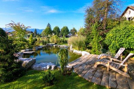 Photo pour Chaises longues près de l'étang dans un beau créatif fleur jardin verdoyant - image libre de droit
