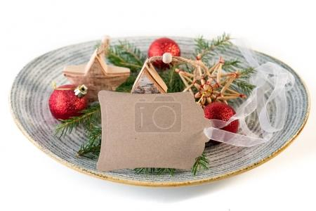 empty card with Christmas decorations and fir branches on plate