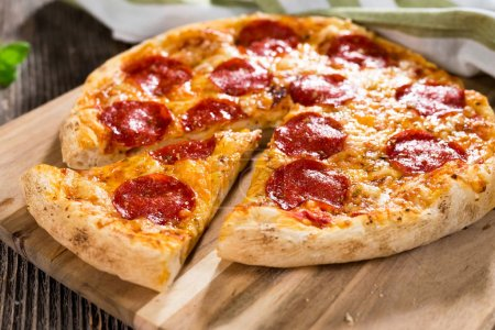 sliced pepperoni pizza on rustic background