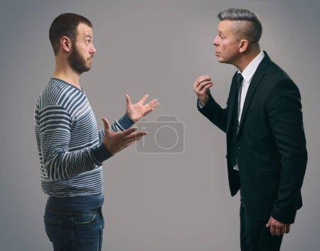 Photo pour Deux hommes d'affaires parler. Studio abattu. Fond gris - image libre de droit