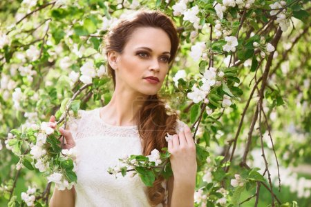 Photo for Beautiful young woman near the blossoming spring apple tree - Royalty Free Image