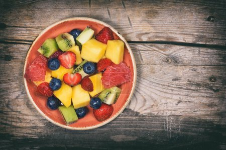 Photo for Delicious fruits salad in plate on wooden table. Top view - Royalty Free Image