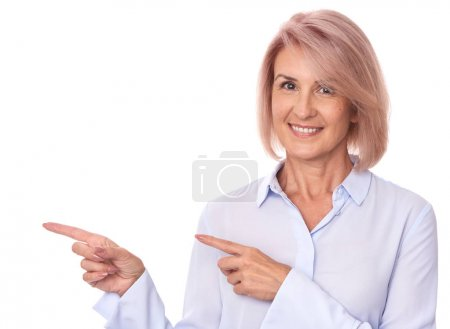 Photo for Beautiful senior woman pointing finger to copy space. Isolated on white - Royalty Free Image