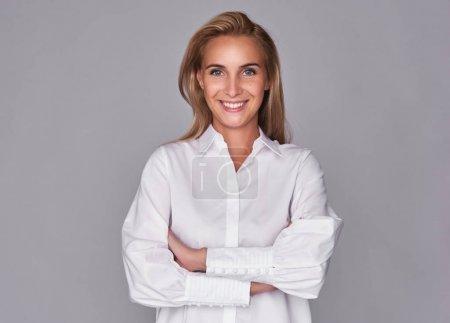 Photo pour Toothy souriant jeune jolie femme les bras croisés. Belle fille isolée sur gris - image libre de droit
