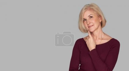 Photo for Portrait of blonde old woman. Care and beauty of hair and skin. Isolated on grey with copy space - Royalty Free Image