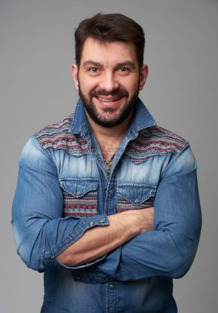 Photo for Confident handsome young bearded man in jeans shirt keeping arms crossed and smiling. Isolated on grey background - Royalty Free Image