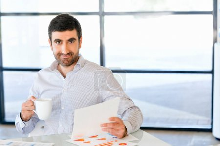 Handsome young man holding paper in office