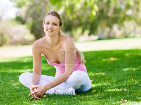 Young healthy woman having a break after exercising in the park