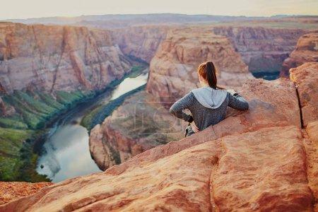 Woman standing on precipice edge at Horseshoe Bend, Arizona, USA