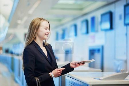 Femme dans un aéroport international au comptoir d'enregistrement, donner son passeport à un agent