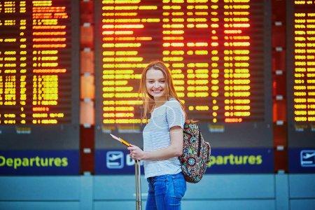 Photo pour Belle jeune fille touristique avec sac à dos et bagages à main à l'aéroport international, près du tableau d'information de vol - image libre de droit