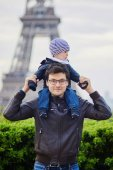 Father holding his son on shoulders near the Eiffel tower