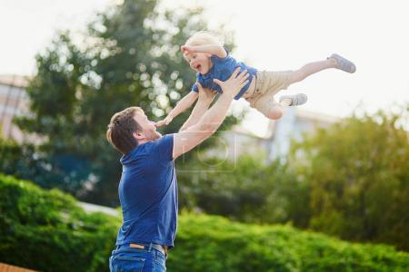 Father throwing his little son up in the air