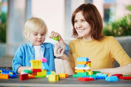Mother playing colorful construction blocks with her son