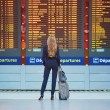 Young elegant business woman with hand luggage in ...