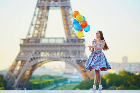 Young woman with bunch of balloons near the Eiffel tower