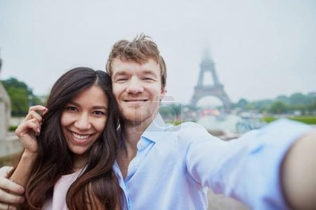 Happy couple taking selfie near the Eiffel tower