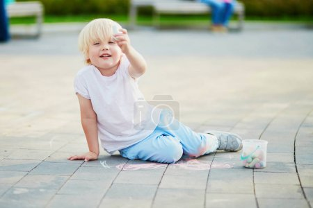 Little boy drawing with chalks on asphalt