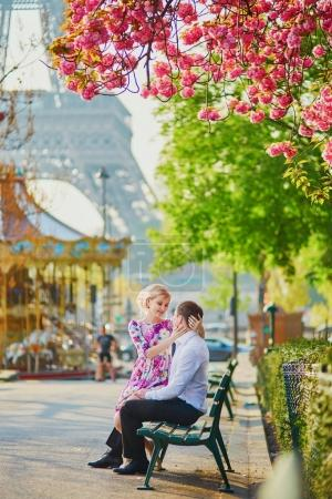 Beautiful romantic couple under blooming cherry tree on a spring day with Eiffel tower in background in Paris, France