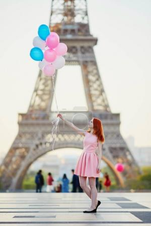 Happy young girl with bunch of pink and blue balloons in front of the Eiffel tower in Paris, France