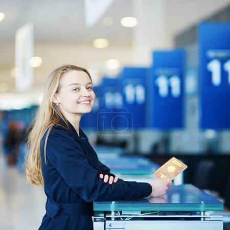 Jeune femme dans un aéroport international au comptoir d'enregistrement, donner son passeport à un agent et en attente de sa carte d'embarquement